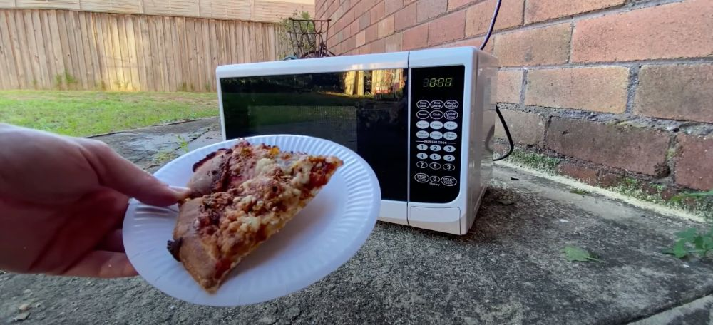 Microwave outside with pizza
