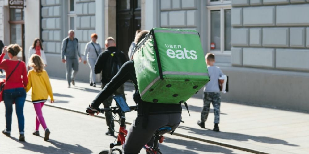 Photo of uber eats delivery bike rider with green backpack